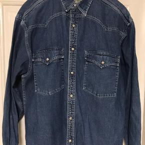 Denim skjorte med trykknapper. Brystvidde: 60 cm. X 2. Længde: 75 cm.