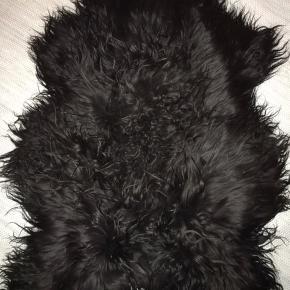 Langhåret sort lammeskind fra Magasin. Nypris 1.000 kr.  Det hvide måler ca. 75x90 cm.
