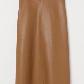 Vid midi-nederdel i imiteret lysebrunt læder fra H&M.  Har en høj talje med trykknapper og skjult lynlås i siden.   Str. 36/S (jeg bruger S-M og passer den). Materiale: uden for. 100% polyester.  Nypris 200 kr.  Sælges for 100 kr. Prisen er fast.