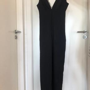 Fin suit i sort med blonder, lynlås og sløjfe. Den er i en str.s. Den er brugt få gange.