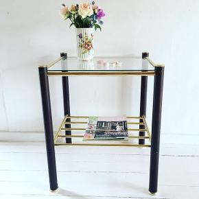 2 borde i pulverlakeret metal og messing, med bordplader i klart glas og med plads til magasiner under bordpladen. Mål: 48x45 cm. H: 57 cm. Bordene koster 300 kr. pr. stk.