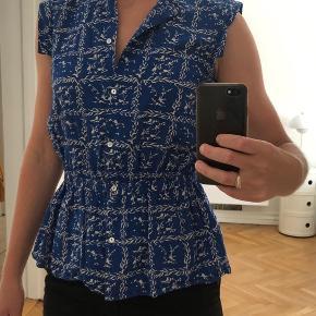 Pæn blå skjorte / bluse med hvidt mønster.  Str. 36. Brugt to gange og fejler intet.   Bytter ikke.  Sendes hvis køber betaler porto.