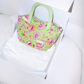 - BENYT 'KØB NU' FUNKTIONEN, VED KØB -  Sommerlig lille grøn håndtaske i stof fra Bulaggi. Tasken har et lyserødt blomstret mønster med perler og palietter på den ene side, små hanke og indvendige lommer til opbevaring. Den lukkes med lynlås øverst.  ○ Mærke: Bulaggi ○ Størrelse: One Size - Højde, med hank: 28,5 centimeter - Højde, uden hank: 17,5 centimeter - Bredde: 30 centimeter - Dybde: 10,5 centimeter ○ Stand: Lettere brugt ○ Fejl/Mangler: Har små pletter inde i foret og mindre mærker udvendigt ○ Materiale: Ukendt - intet invendigt mærke