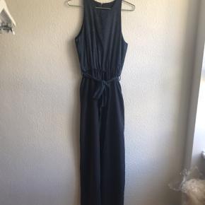 Skræddersyet lang kjole i mørkeblå silke. Skuldre som går langt ind til halsen. Lille hægtelukning i nakken. Langt bindebælte i taljen. Slids bagtil.