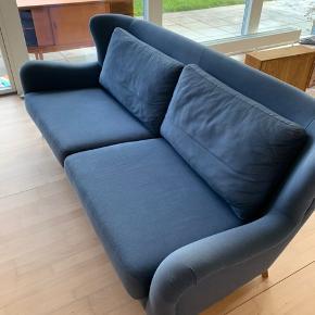 Liva 3 personers sofa fra Idé møbler i blå med ben i eg oliebehandlet. I god stand og ingen pletter. 214 (L) x 86 (H) x 102 (B)  Sædedybde 56 cm Puderne er med lynlås. Sælges pga udskiftning til større sofa. Nypris 8500kr