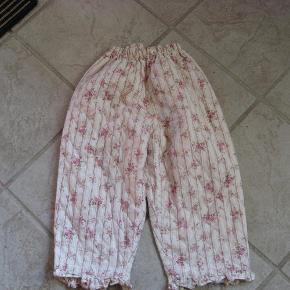 """Vatterede (nærmest som et vattæppe - dvs. tynd kvalitet) bukser med elastik i taljen og flæser ved benene. Rigtige """"tøsebukser"""":).   Se også mine andre annoncer.  Romantiske bukser i lækker liberty stil - pigebukser Farve: beige"""