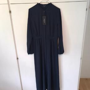 Lang smuk mørk-marineblå maxikjole med skjult knaplukning hele vejen ned og med Underkjole i mørkeblå også. Aldrig brugt.