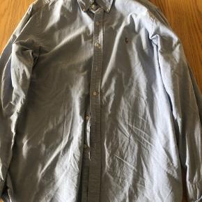 Lyseblå skjorte fra Ralph Lauren: costom fit. Det er str L. Den har kun vært brugt et par gange .