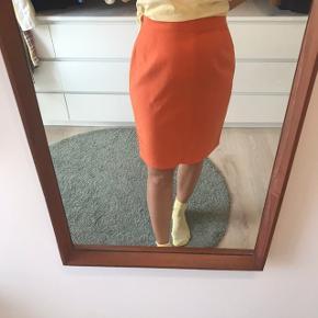 Orange vintage nederdel, lukkes bagpå med lynlås og knap og har en lille slids.