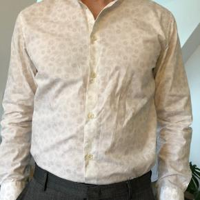 Naturlig stræk og et komfortable snit. Skjorten er brækket hvid med et decent blomstret mønster.  OBS! Ønskes handlen gennemført over TS, afholder køberen gebyret