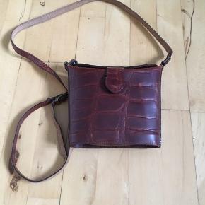 Flot retro belsac taske i brunt læder. Tasken har to rum. Mål: 16 * 19 * 6 cm.
