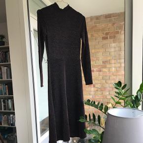 Rigtig flot kjole i sort med glimmer! Den er aldrig brugt og har stadig prismærke i. I lækker strækstof. Sidder til for oven og er løs forneden. Jeg har ikke tid til at tage billede med den på. Derfor sælges den så billigt! :) kan passe en. Xs og s