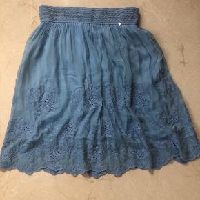 Rigtig sød let nederdel med elastik i taljen. Fejler intet. Går til knæene