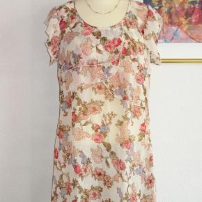 100 % NY: Sød sommerkjole / tunika i tyndt blomstret stof. Materialet er polyester  Brystvidde: 51 cm x 2 Hoftevidde: 61 cm x 2 Længde: 91 cm  Ingen byt, og prisen er fast