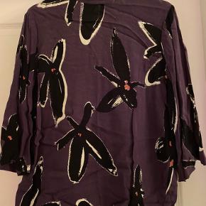 Blommefarvet skjorte med Kina hals og knaplukning i nakken. Blomster i sort/beige/orange som print.  3/4 ærmer