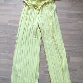 Plisserede gule bukser med bindebånd, som kan fjernes. Mærket er ukendt, men de er aldrig blevet brugt.