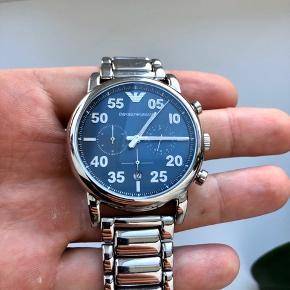 Sælger dette flotte Armani kronografur. Konograf funktionen bruges til at måle et tidsinterval. Urskiven er blå med selvlysende mærker og indelsmarkeringer samt selvlysende visere. Urkassen samt armbåndet er i børstet og poleret stål. Uret er desuden vandbeskyttet ved 5 ATM.