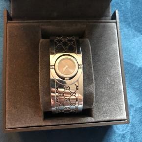 Gucci Twirl ur fra 2007. Skal have nyt batteri og urværk, men fremstår som nyt uden ridser. Skiven kan vendes om, så det kan bruges som armbånd. Købt i magasin i lyngby. Bevis med stempel og modelnummer følger med.
