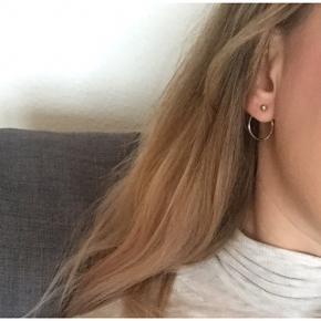 Sølvfarvede øreringe, aldrig brugt. De lukkes så kuglen er foran og ringen er bagpå øret. Ringen måler lige under 2 cm i diameter.  Sender gerne med DAO :)