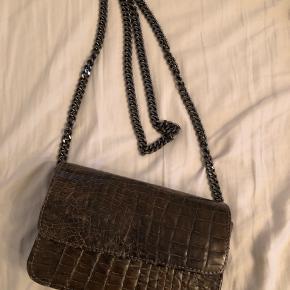 Smukkeste MBOUR Krokodille taske fra Kenzina Skal syes en lille smule ( kan gøre det hvis køber vil ) se billede for 2 sting. Nypris 6000,- Farven er grå og købt i Apair. 20x13x6