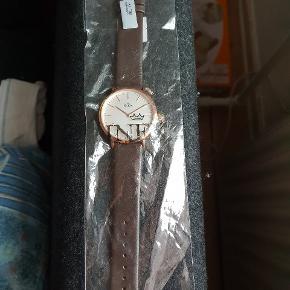 Lækkert Inex ur med læderrem. Urskive ca 40 mm i diameter, kobberfarvet, har aldrig været brugt. Nypris 798.