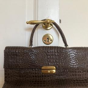 Så fin vintage taske i imiteret slangeskind.  Fejler intet på selve tasken uden på, men plamager i stoffet inden i, da det er en gammel vintage taske. Samt lidt slid på låsen se billede.  Købt i London for 900,- i vintage butik.  Mål: bredte: 34 cm højde: 18 cm dybde: 10 cm.