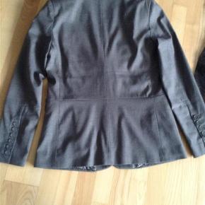 Varetype: Blazer Farve: Grå Prisen angivet er inklusiv forsendelse.  Super fin grå blazer fra Plus Fine, med den hvide T-Shirt (også fra Plus Fine) får man et rigtig fint sæt - begge dele kan købes samlet til kr 300,- Brystvidde 94 cm Længde 65 cm Model: Leon mix blazer 60% polyester 18% wool 19% Rayon 3% Spandex