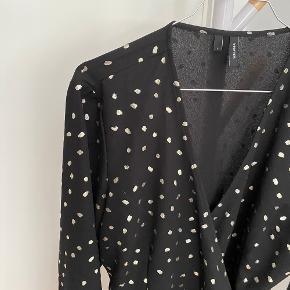 Wrap / slå om bluse fra Vero Moda Med flæse  Farve: sort med guld  Str.: L  Stand: brugt et par gange