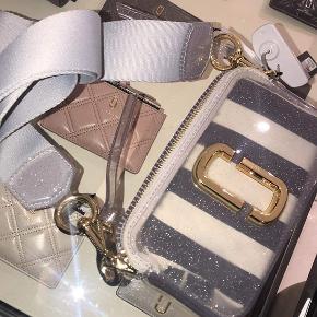 Sælger denne limited edition Marc Jacobs snapshot taske i en sart lilla med glimmer.  der med følger en lille pung, som kan puttes ind i tasken så den ikke længere er transparent.  Nypris 3.600.  Brugt få gange.  BYD gerne.