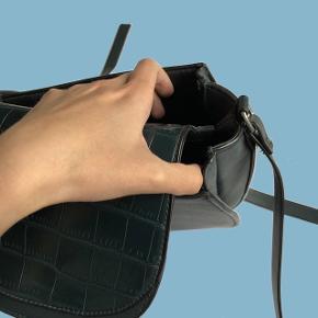 Lækker skuldertaske med justerbar strop og imiteret slangeskind. Der er to identiske rum i tasken, med god plads - en åben og lukket Tasken er brugt men i pæn stand