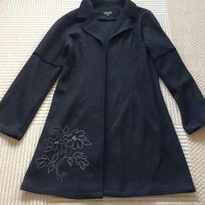 Visual meget lækker sort 35% uldjakke str 38. Lukkes med hægter. Matr 35% uld og 65% viskose.Brystvidde ca 2x47 cm og længde ca 87 cm.
