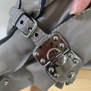 Super lækker tote med masser af plads 40x37cm Ingen synlige skader på skindet. Dog er håndtaget lettere slidt og deraf prisen. Farven er en varm grå/brum. Virkelig en god taske med plads til bærbar m.m Bytter ikke.
