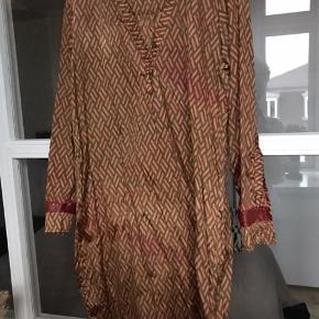 Unika vintage silke kjole syet af silke sari. Den hedder Athen Dress men der er ikke to der er ens.  Da jeg lige havde købt den fik jeg desværre Strøget et lille stykke på ærmet for varmt, men jeg har ikke haft brugt den med ærmerne nede, så det har ikke kunnet ses. Jeg har rullet ærmerne op til albuen.  Sælger den alligevel langt under prisen, pga hullet.   Køber betaler Porto.