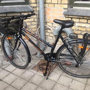 Sort damecykel fra Puck.  7 gear. Med håndbremser, ingen pedalbremse.  Har sammenlagt været brugt tre uger.  Ny kurv og ny kædelås m. to nøgler følger med - kurven er sat på ifm. eftersyn, som den netop har været til. Har kvitteringer på både kurv, lås og eftersyn - desværre ikke cykel. Den blev smurt, fik justeret gear og generelt efterset. Cyklen er derfor fuldstændig klar til brug.   Den kan hentes i København eller Køge.  Spørg endelig! 🚲💨