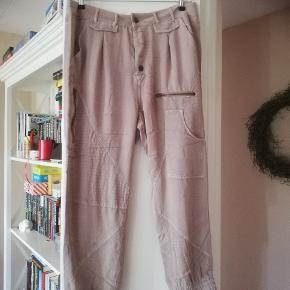 Brugt 1 gang en ellers lækker buks med lidt baggy og elastik i ben.. Buksen er sandfarvet