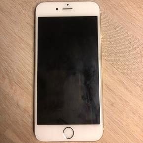 IPhone 6, 16 GB hvid/guld sælges.  OBS. Lader medfølger ikke da den er defekt.   Høretelefoner er næsten som nye.   Har forbrugsridser bagpå som det ses på billedet. Skærmen foran har ingen ridser. Som det ses på et af billederne, er skærmen gået lidt fra i venstre hjørne efter den har været tabt en gang, det gør dog ikke noget for telefonens funktion og ses kun når telefonen ligger.