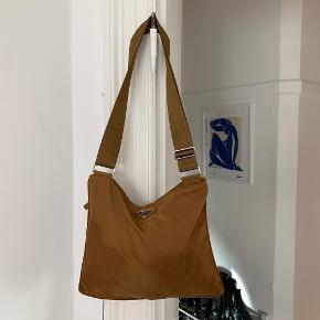 Sej nylon taske i brun. Der er nogle pletter på, som ses på billederne