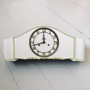 Super fint retro / antik ur.  Det er malet i en råhvid farve med lysegrønne detaljer.   Uret er 50 cm langt, 20 cm højt og 14 cm dybt.  Det trækkes op foran.   Byd gerne 😊  Ur // kaminur // træur// retro // antik