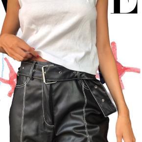 Sorte bukser i læderlook med aftageligt bælte. 100% polyester. De er desværre aldrig blevet brugt - derfor jeg sælger🏍