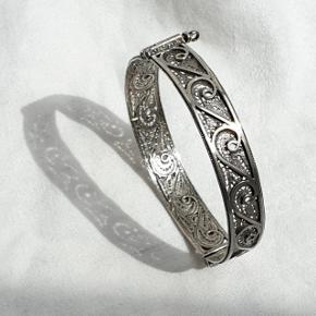 Ældre filigran armbånd i ægte sterling sølv, stemplet 925. Bredden er 1,1 cm, vægten 15,6 g. Indre diameter: 5,7 cm, omkredsen er 17,7 cm. Det kan åbnes i siden.  Se også mine andre annoncer med smykker 🦋