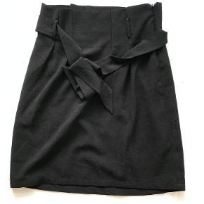 Sort nederdel med bånd.