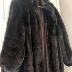 Super fin vintage kunstig pels frakke sælges. Farven er mørkebrun. Den er lavet af akryl—IKKE RIGTIG PELS!  Har knapper foran og lommer. Den er lang og varm, perfekt til vinter.  Længde er 125cm. Jeg er 169cm høj.