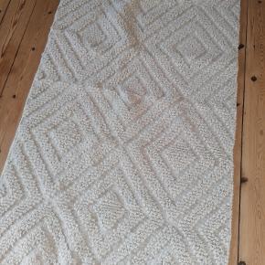 Gulvtæppe fra H&M Home Bredde: 70 cm Længde: 140 cm Brugt få gange.  Ingen trådudtræk. 60 % Uld/ 39 % Bomuld/1 % polyester Kan afhentes i Esbjerg eller sendes på købers regning og ansvar.
