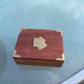 Hej! Jeg sælger denne flotte træ æske, som kan holde 1 sæt spillekort. Udenpå æsken er der et flot mønster, som ses på billedet. Jeg sælger denne æske til 70 kr.  Hvis du har nogle spørgsmål til den, så spørg løs.  Tjek gerne mine andre annoncer ud for en masse billige ting!