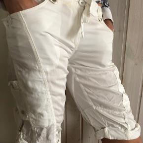 """Shorts, Karen Millen, str. 40, Råhvid, Bomuld & polyester, Næsten som ny  Lækre råhvide shorts fra anerkendte """"Karen Millen"""". Chicke, casual og hip på en og samme tid.  Et hav af klassiske Karen Millen signaturdetaljer ... lommer, bånd, trykknapper, snore, oprulning for neden etc.  Størrelse: EU 40  """"Modellen"""" på billedet er 176cm, 65kg.  Nypris: 125 EUR = ca. 930 kr.  Købt i Rom. Brugt én gang Fremstår rigtig flot."""