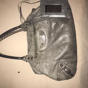 Balenciaga Skuldertaske, Slidt. Vanløse - Rigtig fin og brugbar balenciaga taske. Selve tasken fejler INTET, men læderet på den ene hank er slidt. (Se billede) sælges i en hurtig handel for 950 kr.. Balenciaga Skuldertaske, Vanløse. Slidt, Tydelige tegn på brug og slid. Har mindre skader, men er stadig brugbar. Skal fremgå tydeligt af annoncens billeder eller nævnes i beskrivelsen