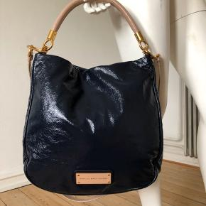 Too hot to handle i patent læder. Jeg har brugt den meget få gange, derfor er i som ny stand. Fejler intet.  Midnight blue farve. Så smuk kombination   med gyldne hardware og beige skulder rem og hank.  Højde: 32 cm.  Bredde 34 cm.  Byttes ikke.