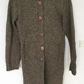 """Varetype: Lang Farve: Brune  Brun/beige/blågrå strikjakke med hætte. Trækker til en """"af-fnuldring"""" , ellers i fin stand. 80% uld 20% polyamid"""