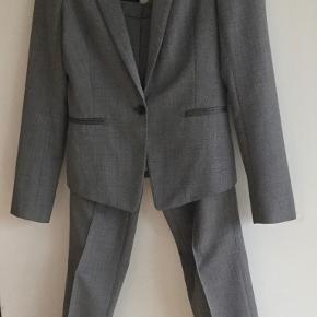 Gråt jakkesæt i uld m sort knap i blazer, creme silkefor og grå skinddetaljer v lommer i str 34-36.