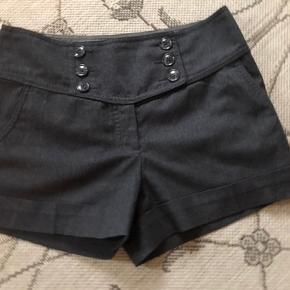 Shorts fra H&M, str.38(passer til str.36-38), farve: mørkegrå, med lommer foran og bagpå, lukkes med lynlås og knapper foran, viscose, elastane, polyester, L.:31 cm. foran og 32 cm. bagpå, brugt kun 1 gang, i meget god stand dom ny.
